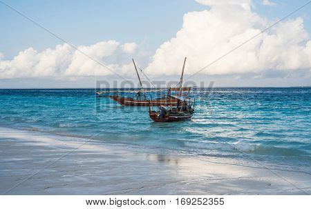 two african boats near the shore with beautiful colorful sea and sky on the background
