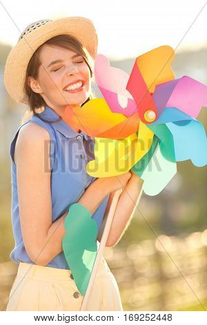 Young happy funny (vintage) dressed woman on the street  with colorful weather vane,looking like flower  Picture ideal for illustating woman magazines.