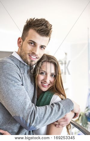 Portrait of loving young man hugging woman at cafe