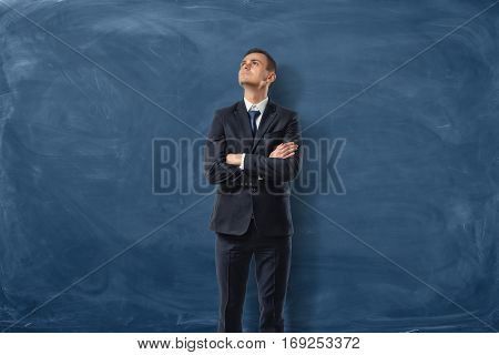 Businessman is staying his arms crossed on blue background of a blackboard. Inner inspiration. Business development. Leadership qualities.