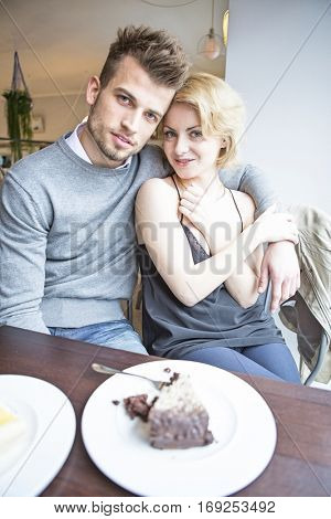Portrait of young couple sitting at cafe table