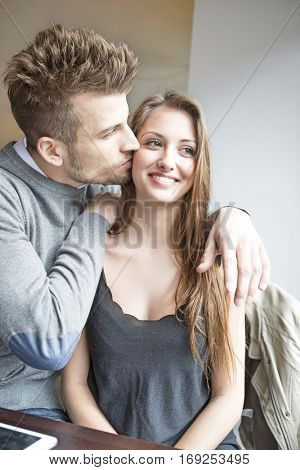 Romantic young man kissing woman in cafe