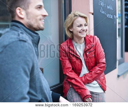Happy young couple sitting outside cafe