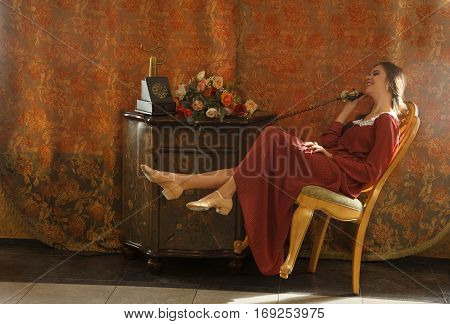 Portrait of sensual young woman in vintage dress indoors in a day light.She sits on the chair which stands on one leg. Professional style and make-up