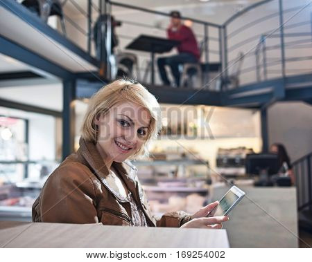 Portrait of smiling young woman using tablet PC in cafe
