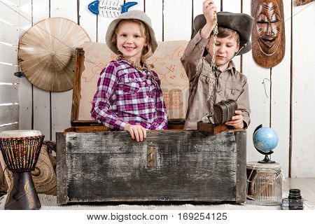 smiling little boy and girl with jewelry sitting in big old chest