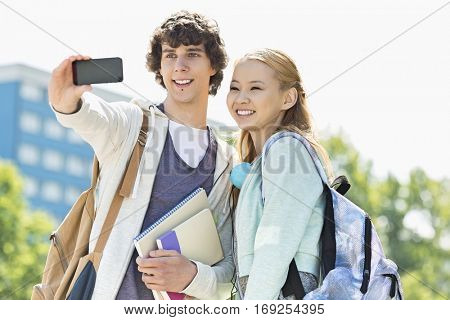 University friends taking selfie with smart phone at campus