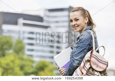 Portrait of happy young female student at college campus