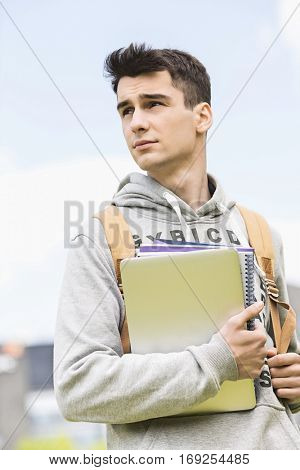 Young male college student holding books while looking away outdoors