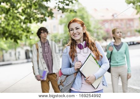 Smiling young female student with friends in background on street