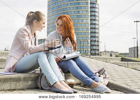 Full length of smiling female college students studying on steps against building