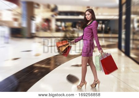 Happy Asian Business Woman Walking While Carrying Shopping Bag