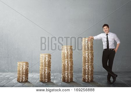 Confident asian businessman standing beside coin stack against grey wall background
