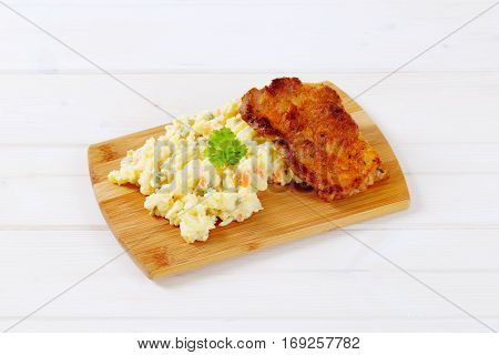 roasted chicken with potato salad on wooden cutting board