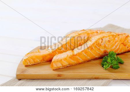 roasted salmon fillets on wooden cutting board - close up