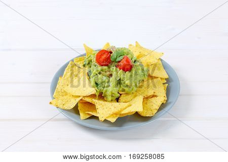 plate of corn tortilla chips with guacamole dip on white background