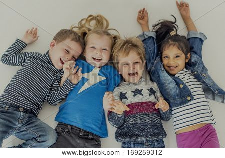 Group of small kids lying on the floor having fun