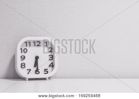 Closeup white clock for decorate show half past six or 6:30 a.m. on white wood desk and cream wallpaper textured background in black and white tone with copy space