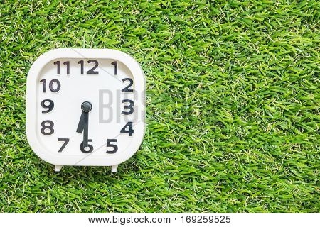 Closeup white clock for decorate show a half past six or 6:30 a.m. on green artificial grass floor textured background with copy space