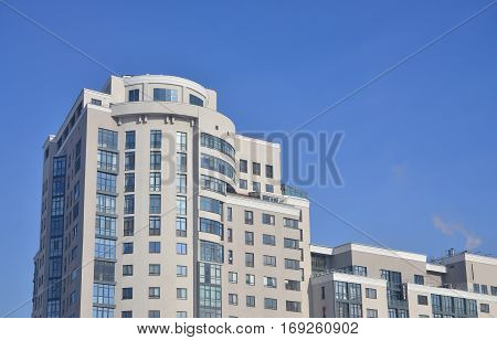 Multi-story office building beige color with lots of glass windows on a background of pure blue sky. Newly built office space for rent