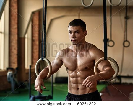 Strong healthy muscular man man working out with gymnastics rings