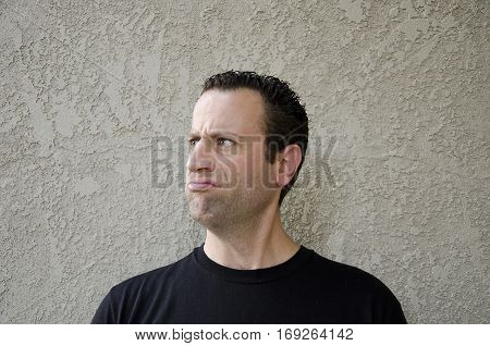 Man making a disgruntled face looking to the left.
