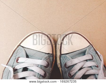 Dirty shoes top view of blue sneakers display on brown background. Vintage effect.