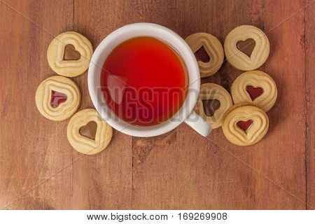 A white cup of tea with butter cookies with heart-shaped chocolate filling, on a dark wooden texture. Selective focus