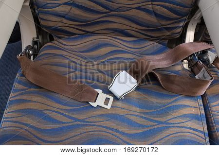 Unbuckled safety belt on chair of airplane