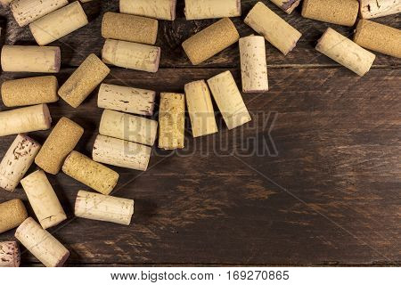 Many wine corks on a dark wooden background texture with copy space. A horizontal design template for a tasting invitation or restaurant menu