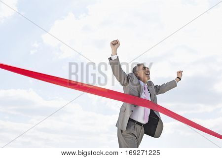 Cheerful businessman crossing finish line against sky