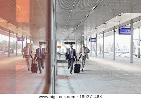 Full length of businessmen with luggage rushing on railroad platform
