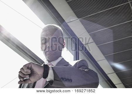 Middle aged businessman checking time at railroad station