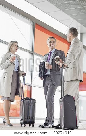 Full length of businesspeople with coffee cups talking on railroad platform