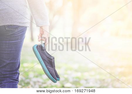 Woman holding black shoes in garden .