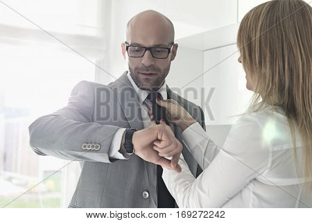 Mid adult businessman checking wristwatch while woman adjusting his tie at home