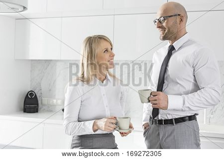 Happy mid adult business couple having coffee in kitchen