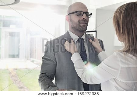 Woman dressing up businessman at home