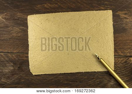 An overhead photo of a piece of old parchment on a dark wooden background texture with a golden ink pen. A mockup or a banner with copy space