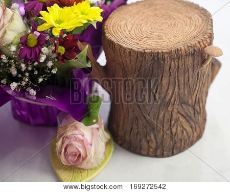 Stump Of Clay Next To A Bouquet Flowers