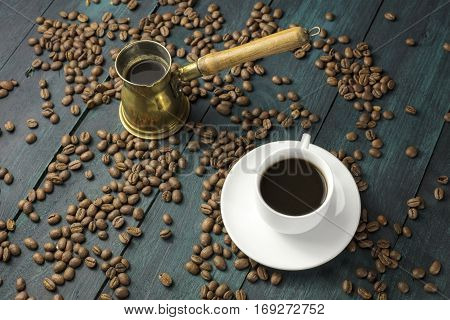 A photo of a cup of black coffee on a wooden boards texture, with a vintage coffee pot, beans scattered around