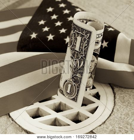 American dollar note doing down the drain with the flag.