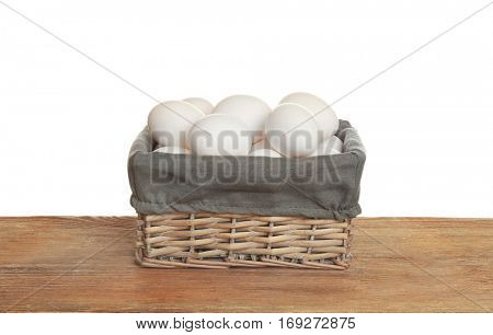 Raw eggs in wicker basket on wooden table