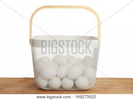Raw eggs in basket on wooden table