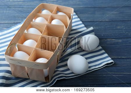 Raw eggs in package and napkin on wooden background