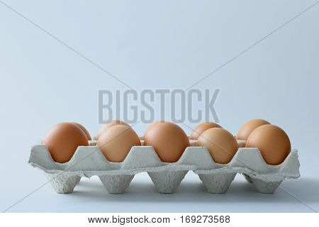 Raw eggs in package on white background