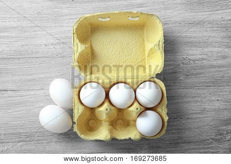 Raw eggs in package on wooden background