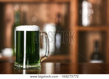 St. Patrick Day concept. Glass of green beer on bar counter