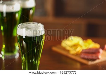 St. Patrick Day concept. Glass of green beer and snacks on bar counter