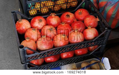 Fresh pomegranates in plastic crate on market
